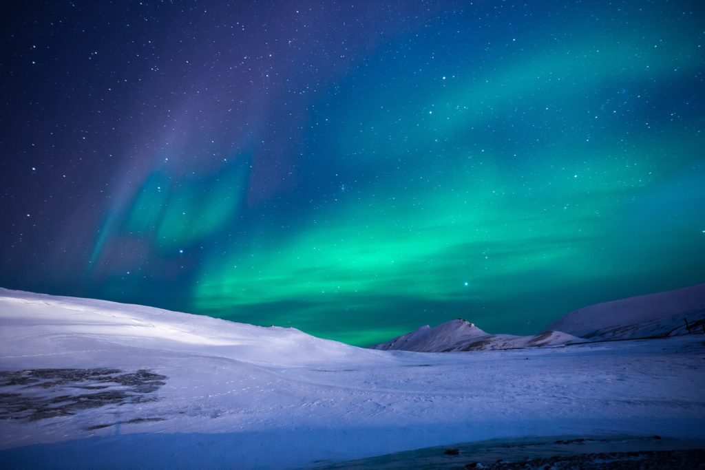 aurora boreal green and purple over snow